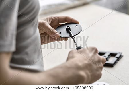 Male is screwing a screw with a screwdriver into a round metal billet on the background of the blurry table in the workshop. Low aperture closeup photo. Horizontal.