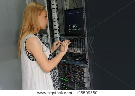 Young Woman Engineer It Technician In The Data Center Server Room.