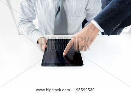 Two businessmen using tablet computer with one hand touching the screen business discussion concept