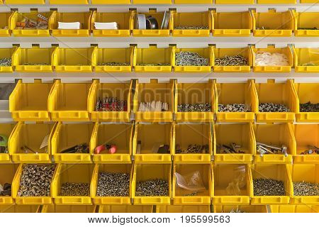 Many plastic yellow boxes are hanging on the light wall in the workshop. Inside them there are screws, nuts, dowels, drillers, lines, pliers, nozzles, insulating tapes, etc. Closeup. Horizontal.