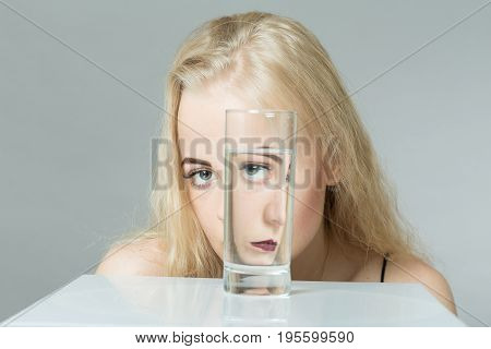 girl looks at camera through glass with water on gray background