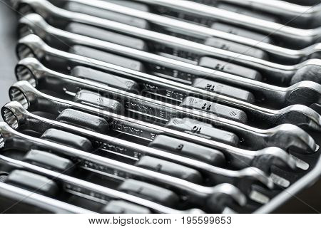 Different sizes chrome spanners in the dark toolbox. Low aperture closeup photo. Horizontal.