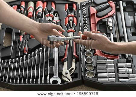 Guy gives to tattooed man a ratchet above the dark toolbox in the workshop. In the toolbox there are black-red pliers and screwdrivers, spanners, saw and different nozzles. Closeup. Horizontal.