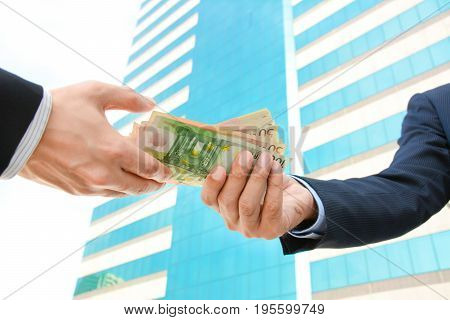 Businessman hands passing money - Euro currency (EUR)