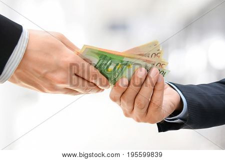 Businessman hands passing money Euro currency (EUR) on white gray background