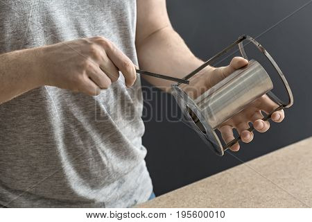 Steel cylindrical construction in the hand of the man near table in the workshop on the dark background. Guy wears a gray T-shirt and has a tattoo. Closeup photo. Horizontal.