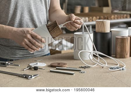 Assembling in the workshop. Man holds a white lamp with a wooden part per the cable. On the table there are other lamp billets, different wrenches, caliber, screws, bushings. Indoors. Closeup.