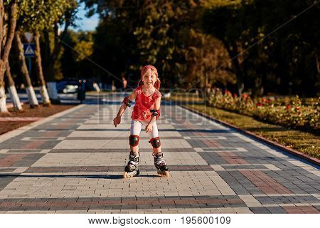 Girl riding on roller skates in skatepark summer outdoor. Child in a red suit for the rollers. Happy childhhood concept