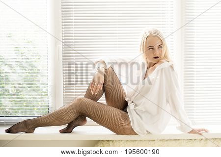 girl in tights sitting on window with blinds in sunlight