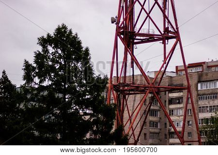 A big broadcasting radio tower inside a russian city with trees and buidings