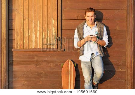 Handsome guy in four season outfit standing on brown wooden background and holding his smartphone - Smiling men in autumn clothes typing on the phone -Teen with longboard connected to social media