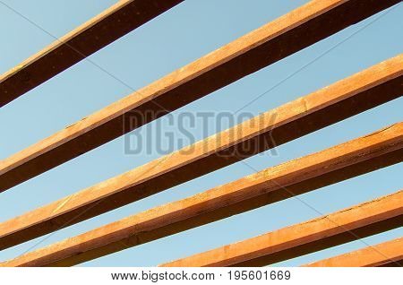 Modern wooden with big pillar and ceiling, wood background. Wooden Decking, bridge made of wooden floors. Old wood frame with a blue sky on the background.