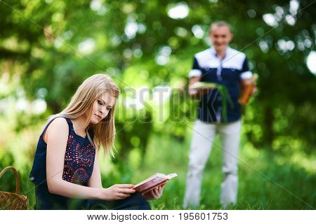 Young lovers on vacation. blonde girl in dark blue dress read the book and man in light trousers with surprise in his hands on background. happy family relationship concept