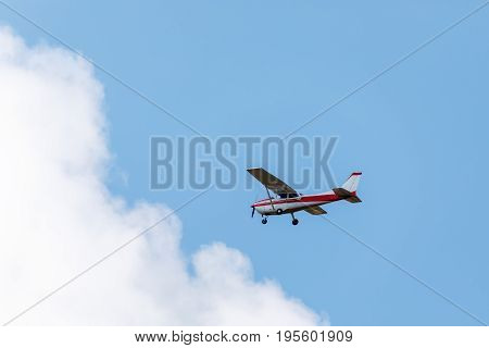 Small sightseeing aircraft in blue sky with white clouds