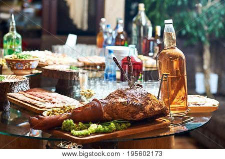 Table full of food and alcohol drinks at the restaurant. Smoked pork served on a wooden plate.