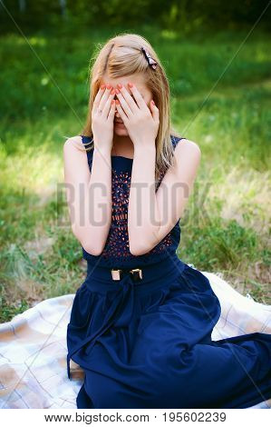 Sad lifestyle portrait of beautiful blond girl closes eyes with her hands. Concept of fear, horror, fright