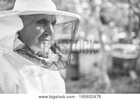 Monochrome shot of an elderly man in beekeeping suit looking away standing outdoors copyspace worker professional beekeeper apiculture farmer farming concept.