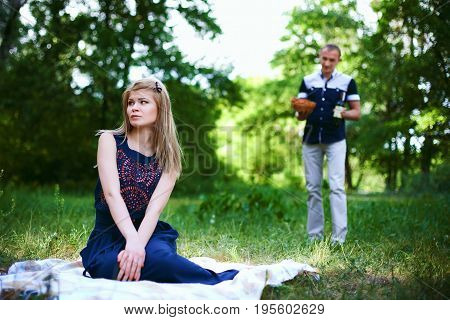 sad girl in dark blue dress sitting on plaid and man on background. Picnic vacation in the forest