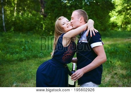 Honeymoon couple in love having fun dating on forest portrait. Beautiful healthy young girlfriend hugging happy boyfriend. Man kissing girl on the cheek.