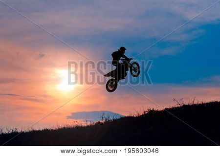 Shot of a motorbike stunt rider jumping in the air on his motorcycle on a beautiful colorful sunset copyspace sport extreme adrenaline riding stunts motocross racing race nature sky dramatic.