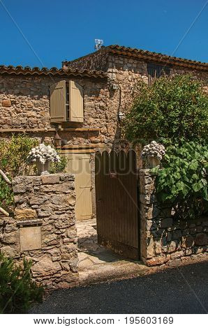 Les Arcs-sur-Argens, France - July 10, 2016. Close-up of old stone house with wooden gate, at the gorgeous medieval hamlet of Les Arcs-sur-Argens. Provence region, Var department, southeastern France