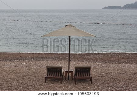 Two sunbeds and umbrella with small table on the empty beach