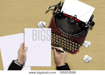 Vintage typewriter with author hand checking a paper sheets