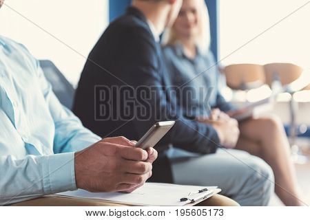 Close up of hands of man sitting on chair in office hall and holding mobile phone by both hands. He is typing sms and leaning arms on clip board lying on laps. Other applicants on background