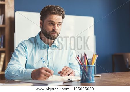 Waist up portrait of serious young man with beard sitting at table in office. He is writing something on piece of paper by pen and thinking about task. Copy space in right side