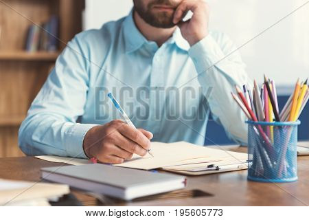 Close up of hands and body of bearded man sitting at table and writing some task by pen on prepare. He is leaning his cheek on one hand
