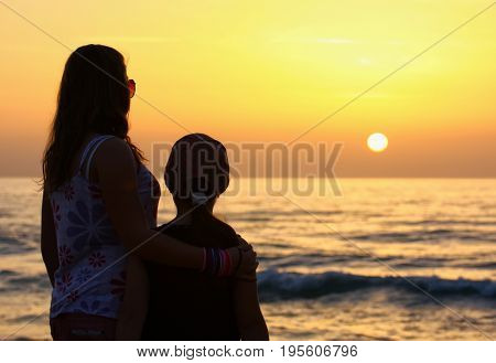 Two girlfriends in the evening on the shore of the Mediterranean Sea