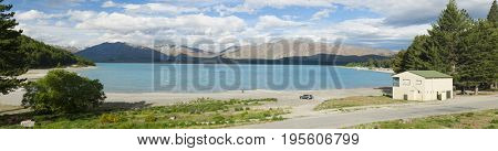 Beautiful incredibly blue lake Tekapo and mountains, Southern Alps, on the other side. New Zealand, panoramic photo