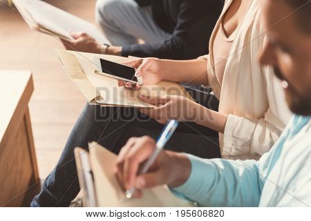 Close up of hands of men and woman with papers sitting on chairs in company office. Girl is holding mobile phone and writing sms. One guy with clip board is making notes by pen. Focus on gadget