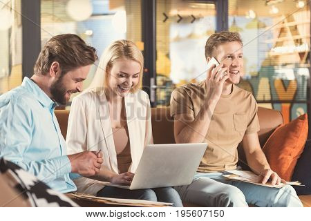 Cheerful young lady with laptop and two men with papers are sitting on sofa in hall and communicating with each other. Bearded guy is rolling pen in hands and other male is talking via cellphone