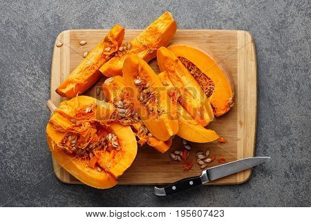 Chopped pumpkin with seeds on wooden cutting board, top view