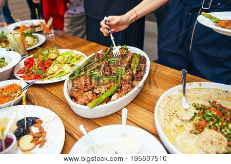 Women's Hands Pile Themselves A Meal In A Plate Of Lunch. The Concept Of Nutrition. Buffet. Food. Di