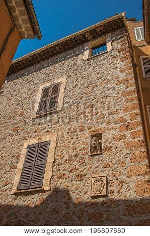 Stone wall with closed windows and gargoyle in niche, at the gorgeous medieval hamlet of Les Arcs-sur-Argens, near Draguignan. Located in the Provence region, Var department, southeastern France