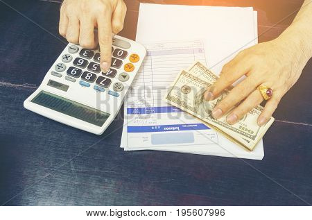 Local businessman using calculator figuring out total price of merchandises paid by US dollar bills