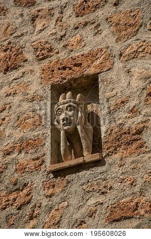 Close-up of stone wall with gargoyle in niche, at the gorgeous medieval hamlet of Les Arcs-sur-Argens, near Draguignan. Located in the Provence region, Var department, southeastern France