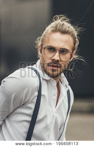 Close-up Portrait Of Handsome Stylish Young Man In Spectacles And Suspenders Looking Away
