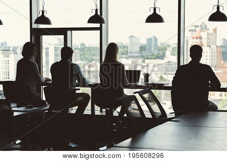 Young men and women are sitting on office chairs in line at one long desktop facing huge windows. Big round chandeliers hanging over workplace on metal chains. Dark shadow and focus on their back