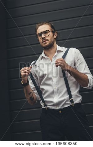 Handsome Stylish Man In Spectacles Adjusting Suspenders And Looking Away