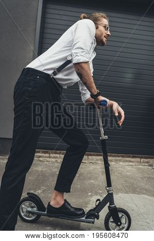 Side View Of Stylish Young Man Wearing Eyeglasses And Suspenders Riding Scooter