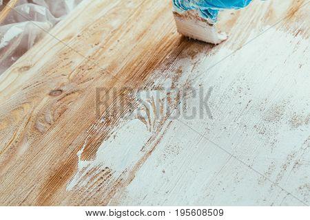 closeup hand use brush paint white on wood surface.