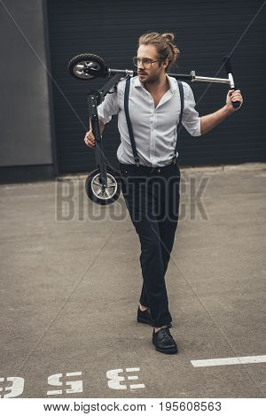 Handsome Stylish Young Man In Spectacles Holding Scooter And Looking Away