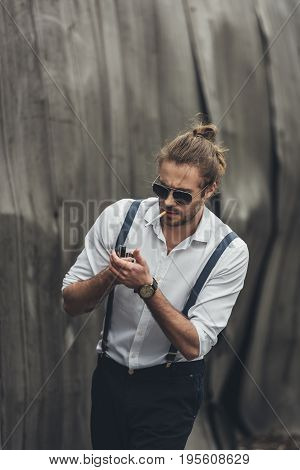 Portrait Of Handsome Stylish Bearded Man In Sunglasses And Suspenders Lighting Cigarette With Lighte