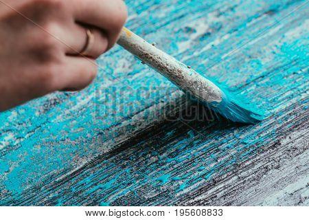 closeup hand use brush paint white blue on wood surface.