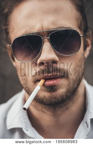 Close-up Portrait Of Handsome Bearded Young Man In Sunglasses Smoking Cigarette