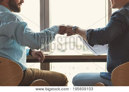 Close up of hands of two men sitting at table close to windows. They are turning to each other and touching friendly fists of each other