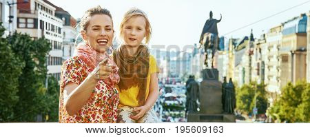 The spirit of old Europe in Prague. happy young mother and child tourists in Prague Czech Republic pointing in camera